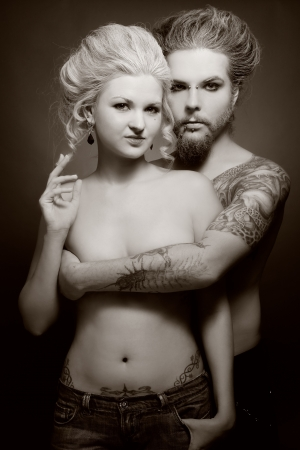 modifying: Duotone shot of pierced tattooed man and woman with old-fashioned make-up and hairstyle