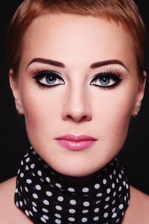 Close-up portrait of young attractive redhead woman with trendy stylish make-up photo