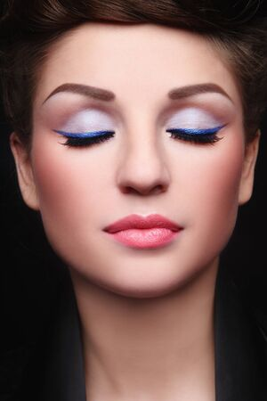 Close-up portrait of young beautiful woman with stylish make-up and closed-eyes photo