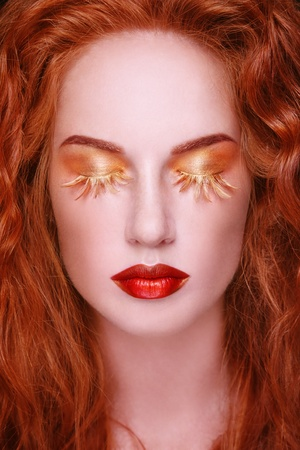 Close-up portrait of young beautiful redhead woman with fancy fake eyelashes photo