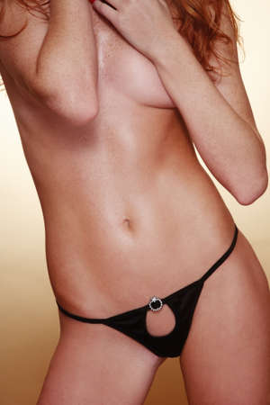 Torso of slim sexy tanned hot redhead girl in black panties Stock Photo - 8317283