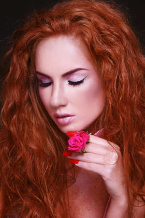Portrait of young beautiful woman with long curly red hair photo