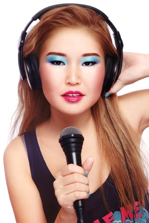 Beautiful stylish asian girl singing karaoke with microphone in hand, on white background photo