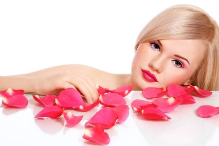 Clear fresh image of young beautiful blond girl with pink rose petals on white background, copy space above Stock Photo - 8473391
