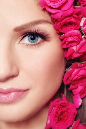 Close-up shot of young beautiful woman face with pink roses in hair photo