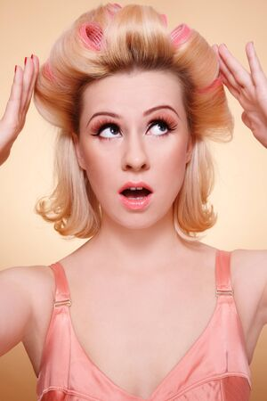 Humorous emotional portrait of beautiful young woman with curlers in hair looking upwards with worried expression photo