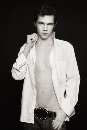 heartbreaker: Tiro de duotono de hombre joven sexy delgado y elegante en camisa blanca y jeans