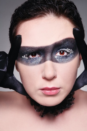 Humorous portrait of young woman with fancy mask painted on her face and incredulous expression photo