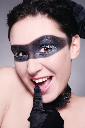 Humorous portrait of young woman with fancy mask painted on her face and funny expression photo