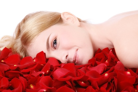 Clear fresh image of young beautiful blond smiling woman with red rose petals on white background, copy space above Stock Photo - 8951446