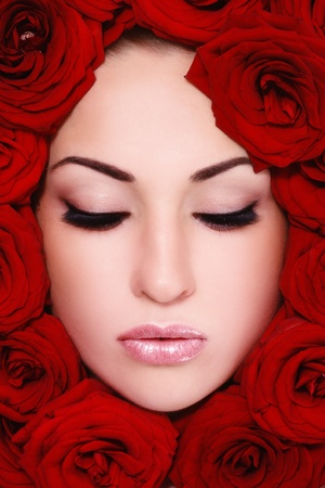 Close-up shot of young beautiful woman face with red roses around photo