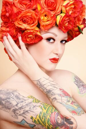 Beautiful sexy glamorous girl with tattoos and fancy wig of bright orange roses photo