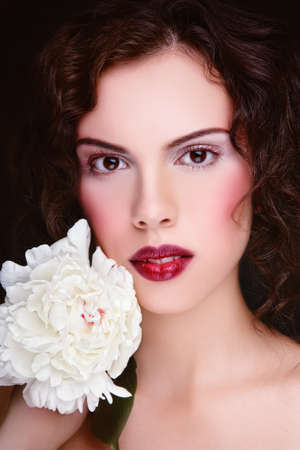 Portrait of young beautiful woman with fancy make-up and white peony in hand Stock Photo - 9026774