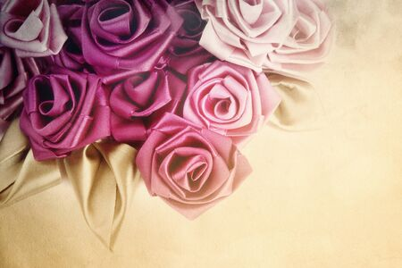 vintage roses: Handmade silk roses on vintage damaged grainy background with copy space below Stock Photo
