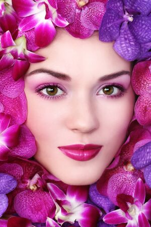 Close-up shot of young beautiful woman face with bright orchids around Stock Photo