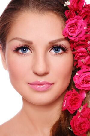 Close-up portrait of young beautiful smiling woman with roses in hair photo