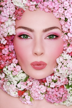 Portrait of young beautiful fresh girl with stylish make-up and pink flowers around her face photo