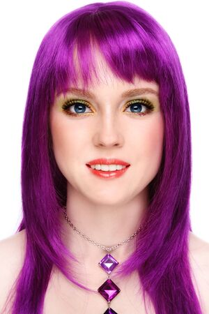 Portrait of beautiful young smiling girl with fancy bright make-up and violet wig, on white background
