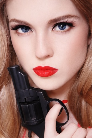 Close-up portrait of young beautiful sexy blond woman with revolver in hand Stock Photo