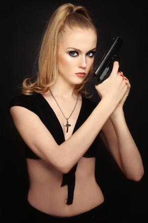 Beautiful slim sexy stylish blond girl with pistol Stock Photo - 9365658