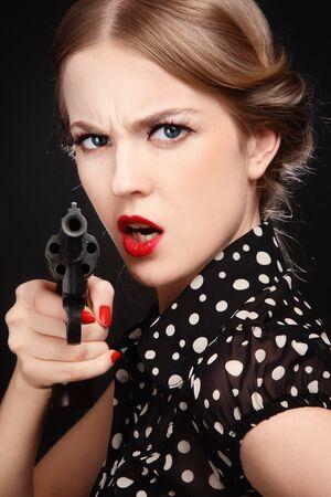 mujer enojada: Retrato emocional de la hermosa joven mujer rubia enojada con revólver en mano