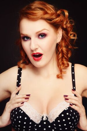 sexy breasts: Beautiful young sexy redhead woman in vintage polka dot bra