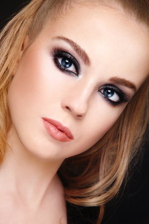 Close-up portrait of young beautiful blond girl with trendy make-up photo