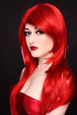 Portrait of young beautiful girl with long red hair and fancy make-up photo