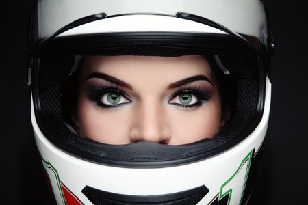 Close-up portrait of beautiful woman with stylish makeup in biker helmet photo