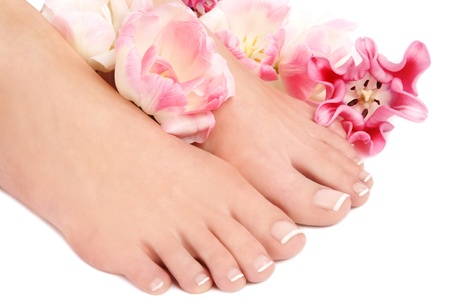 Close-up shot of beautiful woman feet with french pedicure and pink flowers around