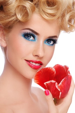 Close-up portrait of young beautiful blond woman with fancy make-up and red flower in hand, on white background Stock Photo
