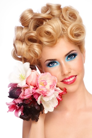 Portrait of young beautiful smiling happy blond woman with fancy make-up and flowers in hand on white background