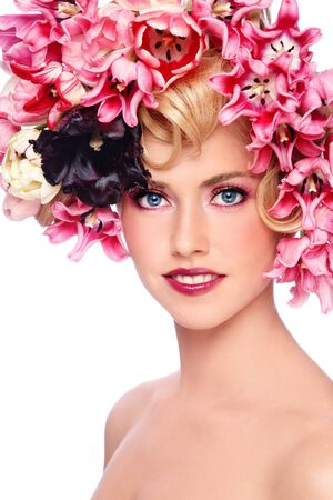 Portrait of young beautiful smiling girl with stylish make-up and colorful flowers on her hair