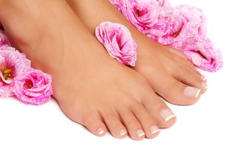 nail care: Close-up shot of woman tanned feet with french pedicure and pink flowers around on white background, selective focus