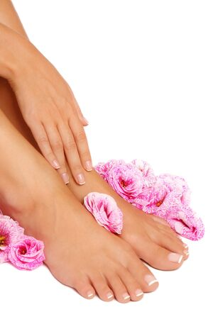 Beautiful woman tanned feet with french pedicure and pink flowers around on white background, focus on hand Stock Photo
