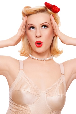 pinup girl: Beautiful sexy blond girl in vintage lingerie looking upwards with surprised expression, on white background