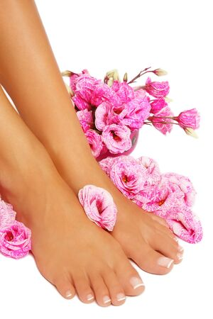 french pedicure: Feet of tanned woman with french pedicure and pink flowers around, on white background