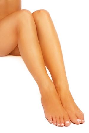 pedicure: Gambe lisce dei conciate donna sottile con pedicure francese, su sfondo bianco Archivio Fotografico