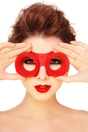 Yong beautiful girl with stylish make-up and old-fashioned red swimming goggles, on white background photo