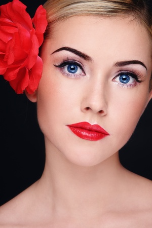 red lipstick: Portrait of young beautiful blond woman with red lipstick and red flower in her hair