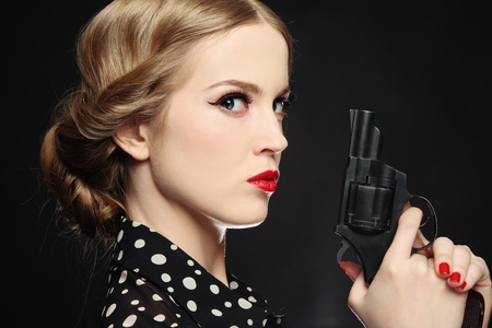 revolver: Portrait of beautiful young angry blond woman with revolver in hand Stock Photo