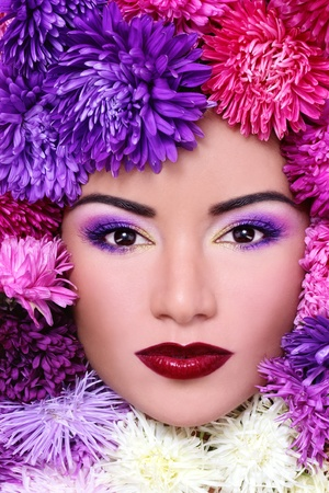 Close-up portrait of beautiful woman with bright make-up and flowers around her face Stock Photo - 10697133