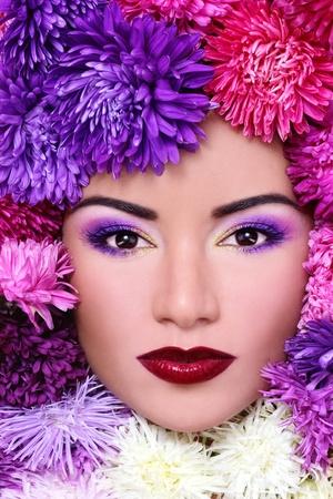 salud sexual: Retrato de primer plano de hermosa mujer con maquillaje brillante y flores alrededor de su cara