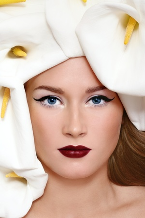 Close-up portrait of beautiful woman with stylish make-up and white flowers around her face photo