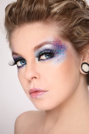 piercing: Close-up portrait of beautiful young woman with stylish hairdo and fancy make-up