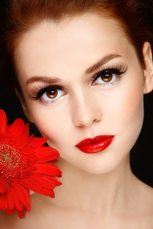 Portrait of young beautiful woman with stylish make-up and red gerbera photo