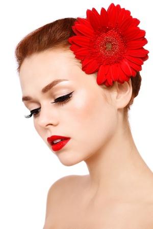 pelirrojas: Retrato de joven mujer hermosa con maquillaje elegante y gerbera rojo sobre fondo blanco