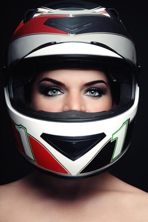 Portret van mooie vrouw met stijlvolle make-up in biker helm Stockfoto