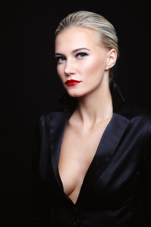 coloration: Young beautiful blond glamorous woman in black silky jacket over dark background