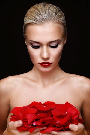 Young beautiful sexy blond woman with red rose petals in hands Stock Photo